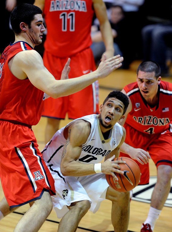 . Askia Booker of CU tries to shoot with Matt Korcheck of Arizona defending during the second half of the February 22, 2014 game in Boulder, Colo.  Cliff Grassmick / February 22, 2014