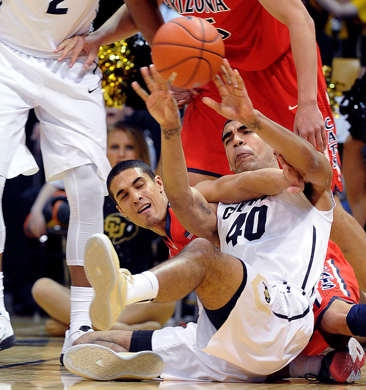 . Nick Johnson, left,  of Arizona and Josh Scott of Colorado,  go to the floor to get a loose ballduring the first half of the February 22, 2014 game in Boulder, Colo.  Cliff Grassmick / February 22, 2014