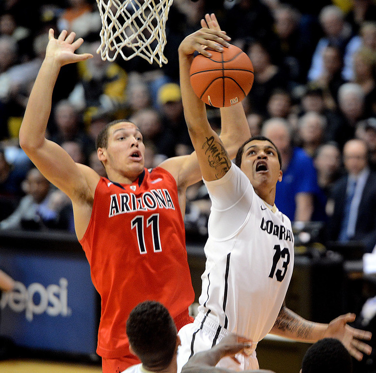 . Dustin Thomas (13) of Colorado, grabs a rebound in front of Aaron Gordon of Arizona during the first half of the February 22, 2014 game in Boulder, Colo.  Cliff Grassmick / February 22, 2014