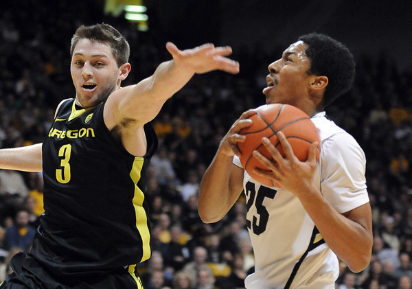 """Spencer Diwiddie of Colorado, drives past Garrett Sim of Oregon<br /> during the first half of the February 4, 2012 game in Boulder.<br /> For more photos of the game, go to  <a href=""""http://www.dailycamera.com"""">http://www.dailycamera.com</a>.<br /> February 4, 2012 / Cliff Grassmick"""