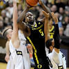 """Olu Ashaolu of Oregon drivs past Shane Harris-Tunks, left, and Carlon Brown, both of Colorado during the first half of the February 4, 2012 game in Boulder.<br /> For more photos of the game, go to  <a href=""""http://www.dailycamera.com"""">http://www.dailycamera.com</a>.<br /> February 4, 2012 / Cliff Grassmick"""