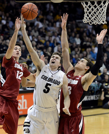 "University of Colorado's Eli Stalzer takes a shot over Rosco Allen, No. 12, and Dwight Powell, at right, during a game against Stanford on Thursday, Jan. 24, at the Coors Event Center on the CU campus in Boulder. For more photos of the game go to  <a href=""http://www.dailycamera.com"">http://www.dailycamera.com</a><br /> Jeremy Papasso/ Camera"