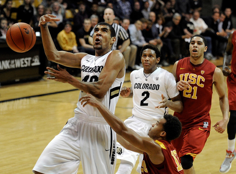 "University of Colorado's Josh Scott gets fouled by Chass Bryan while going for a layup during a game against the University of Southern California on Thursday, Jan. 10, at the Coors Event Center on the CU campus in Boulder. For more photos of the game go to  <a href=""http://www.dailycamera.com"">http://www.dailycamera.com</a><br /> Jeremy Papasso/ Camera"