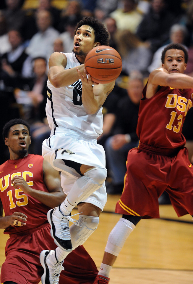 Askia Booker of Colordo drives past  Chass Bryan (13) of USC during the second half of the January 10, 2013 game in Boulder.<br /> Cliff Grassmick / January 10, 2013