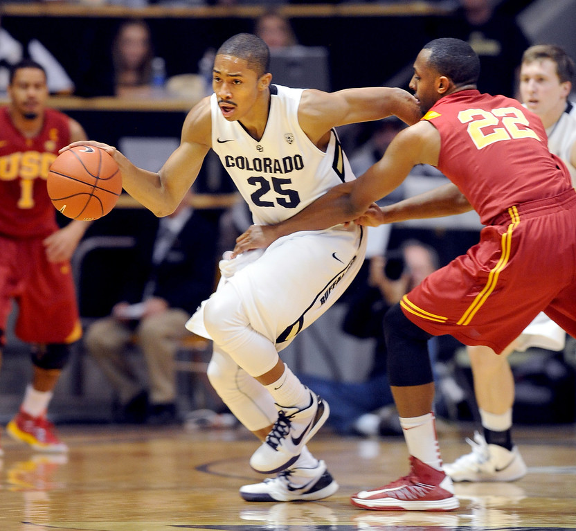 Spencer Dinwiddie of Colorado is held up by Byron Wesley of Southern California during the first half of the January 10, 2013 game in Boulder.<br /> Cliff Grassmick / January 10, 2013