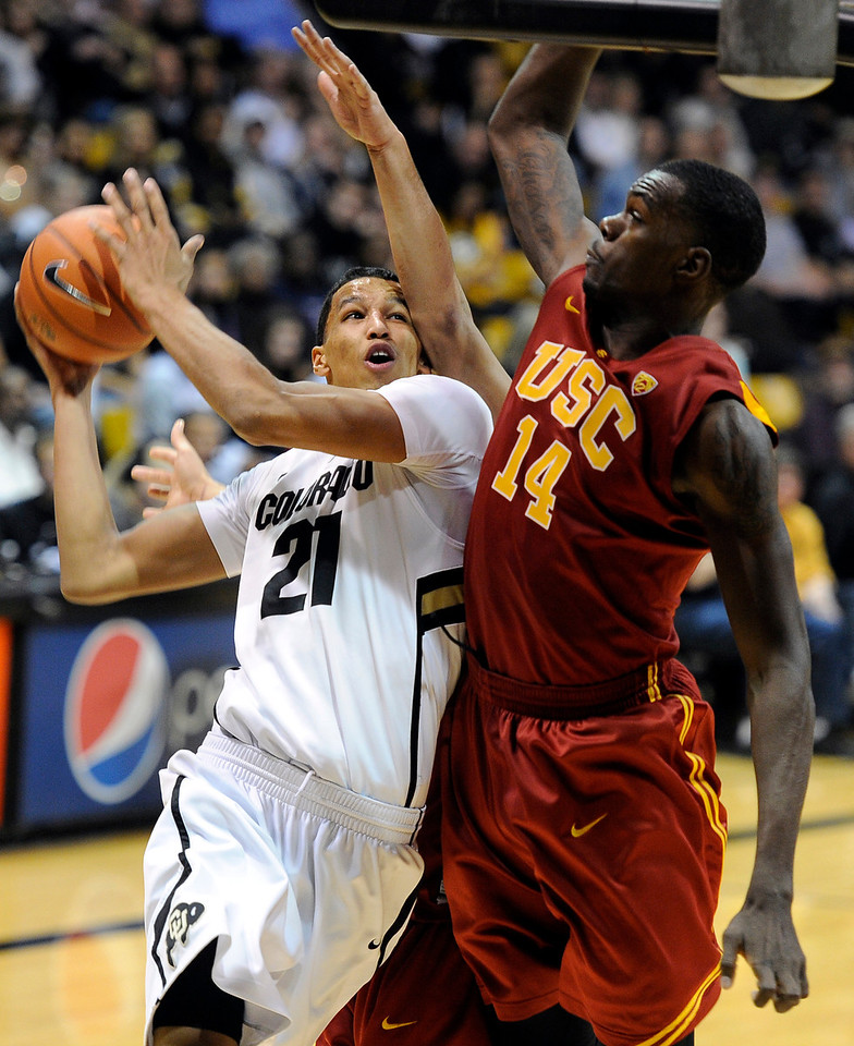 "University of Colorado's Andre Roberson drives to the hoop past DeWayne Dedmon, No. 14, during a game against the University of Southern California on Thursday, Jan. 10, at the Coors Event Center on the CU campus in Boulder. For more photos of the game go to  <a href=""http://www.dailycamera.com"">http://www.dailycamera.com</a><br /> Jeremy Papasso/ Camera"