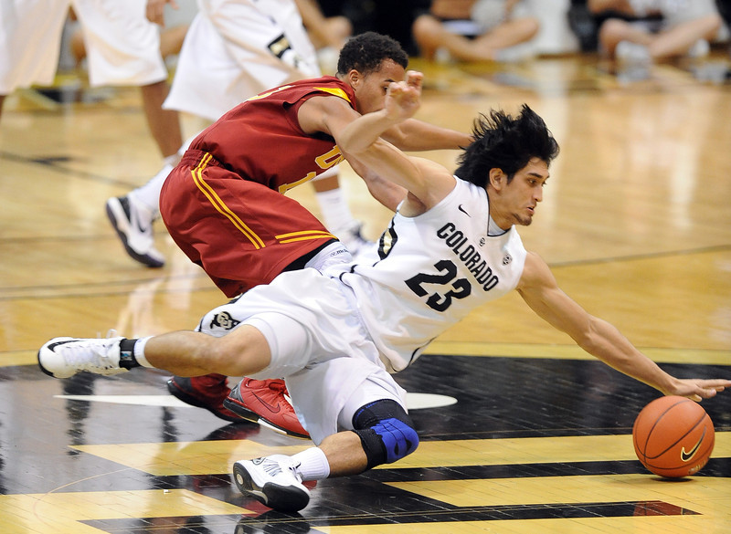 Sabatino Chen (23) slides in to take the ball away from Chass Bryan of USC during the second half of the January 10, 2013 game in Boulder.<br /> Cliff Grassmick / January 10, 2013
