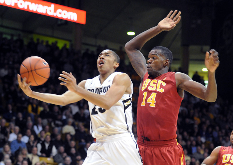 Spencer Dinwiddie of Colorado drives past DeWayne Dedmon of Southern California during the first half of the January 10, 2013 game in Boulder.<br /> Cliff Grassmick / January 10, 2013