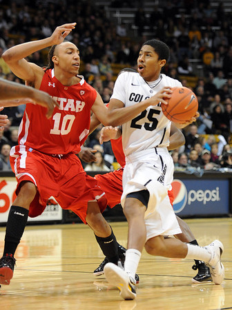 """Spencer Dinwiddie of Colorado, drives on Dijon Farr of Utah <br /> during the first half of the December 31, 2001 game in Boulder.<br /> For more photos of the game, go to  <a href=""""http://www.dailycamera.com"""">http://www.dailycamera.com</a>.<br /> December 31, 2011 / Cliff Grassmick"""