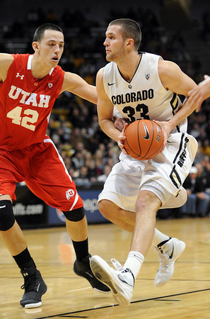 """Austin Dufault of Colorado drives on Jason Washburn of Utah<br /> during the first half of the December 31, 2001 game in Boulder.<br /> For more photos of the game, go to  <a href=""""http://www.dailycamera.com"""">http://www.dailycamera.com</a>.<br /> December 31, 2011 / Cliff Grassmick"""