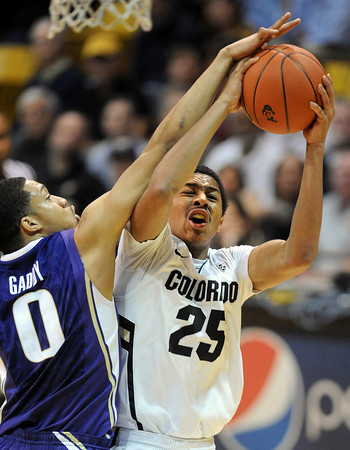 """Spencer Dinwidie of Colorado is fouled by Abdul Gaddy of Washington during the second half of the January 5, 2012 game in Boulder.<br /> For more photos of the game, go to  <a href=""""http://www.dailycamera.com"""">http://www.dailycamera.com</a>.<br /> January 5, 2012 / Cliff Grassmick"""