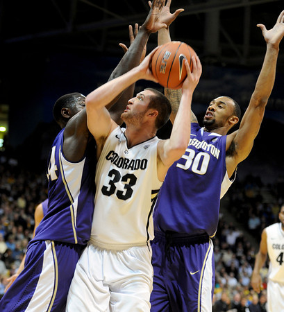"""Austin Dufault (33) of Colorado, is trapped by Darnell Gant, left, and Desmond Simmons, both of Washington,<br /> during the first half of the January 5, 2012 game in Boulder.<br /> For more photos of the game, go to  <a href=""""http://www.dailycamera.com"""">http://www.dailycamera.com</a>.<br /> January 5, 2012 / Cliff Grassmick"""