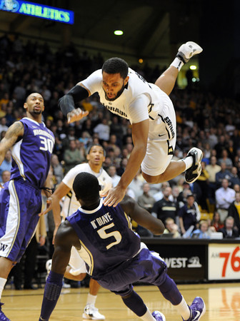 """Carlon Brown of CU flies over Aziz N'Diaye of Washington<br /> during the first half of the January 5, 2012 game in Boulder.<br /> For more photos of the game, go to  <a href=""""http://www.dailycamera.com"""">http://www.dailycamera.com</a>.<br /> January 5, 2012 / Cliff Grassmick"""