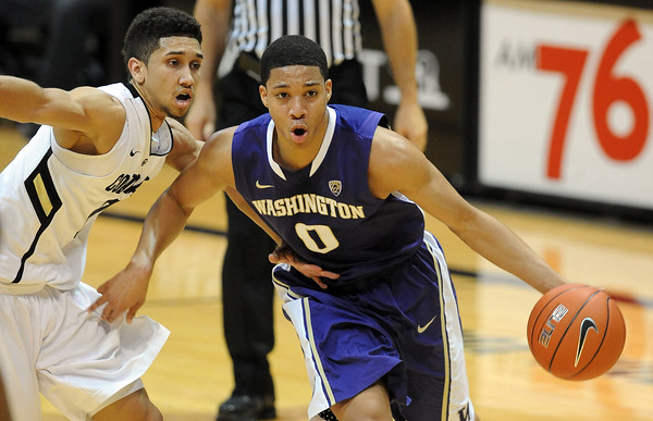 """Abdul Gaddy, right, of Washington, dribbles around Askia Booker of Colorado during the first half of the January 5, 2012 game in Boulder.<br /> For more photos of the game, go to  <a href=""""http://www.dailycamera.com"""">http://www.dailycamera.com</a>.<br /> January 5, 2012 / Cliff Grassmick"""