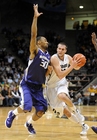 """Austin Dufault of CU drives past Desmond Simmons of Washington<br /> during the first half of the January 5, 2012 game in Boulder.<br /> For more photos of the game, go to  <a href=""""http://www.dailycamera.com"""">http://www.dailycamera.com</a>.<br /> January 5, 2012 / Cliff Grassmick"""