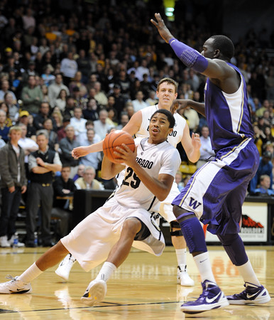"""Spencer Dinwiddie of CU, slips down while driving on Aziz N'Diaye of Washington during the first half of the January 5, 2012 game in Boulder.<br /> For more photos of the game, go to  <a href=""""http://www.dailycamera.com"""">http://www.dailycamera.com</a>.<br /> January 5, 2012 / Cliff Grassmick"""