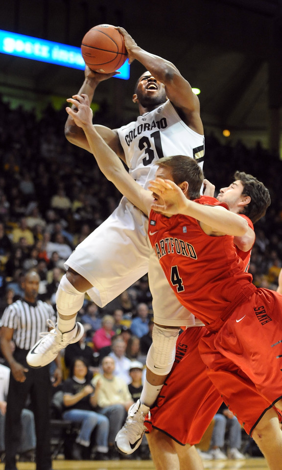 "Jeremy Adams of CU goes to the basket on Corban Wroe of Hartford, during the first half of the December 29, 2012 game in Boulder.<br /> For more photos of the game, go to  <a href=""http://www.dailycamera.com"">http://www.dailycamera.com</a>.<br /> Cliff Grassmick / December 29, 2012"