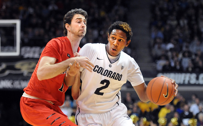 "Xavier Johnson of CU , drives on John Peterson of Hartford, during the first half of the December 29, 2012 game in Boulder.<br /> For more photos of the game, go to  <a href=""http://www.dailycamera.com"">http://www.dailycamera.com</a>.<br /> Cliff Grassmick / December 29, 2012"