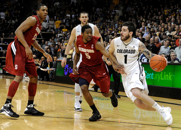 "University of Colorado's Nate Tomlinson drives past Stanford University's Chasson Randle during a basketball game on Thursday, Feb. 23, at the Coors Event Center on the CU campus in Boulder. For more photos of the game go to  <a href=""http://www.dailycamera.com"">http://www.dailycamera.com</a><br /> Jeremy Papasso/ Camera"