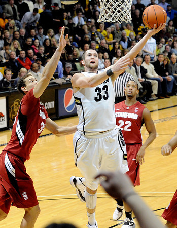 """University of Colorado's Austin Dufault takes a shot over Stanford University's Dwight Powell, left, during a basketball game on Thursday, Feb. 23, at the Coors Event Center on the CU campus in Boulder. For more photos of the game go to  <a href=""""http://www.dailycamera.com"""">http://www.dailycamera.com</a><br /> Jeremy Papasso/ Camera"""