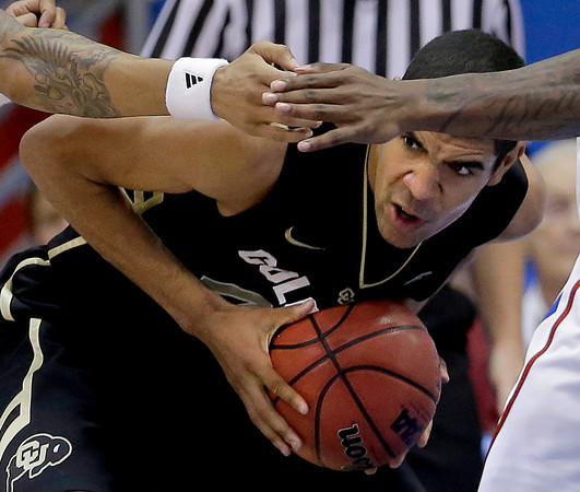 Colorado forward Josh Scott (40) looks for a teammate to pass to under the arms of a couple of Kansas defenders during the first half of an NCAA college basketball game Saturday, Dec. 8, 2012, in Lawrence, Kan. (AP Photo/Charlie Riedel)