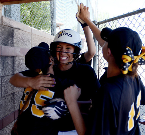 "Mallory Paulson, center, of the Colorado Stars hit a home run to help her team beat the California Stars and qualify for nationals.  She is congratulated by Michaela Good, left, and Sara Good in the dugout.<br /> For more photos of the game, go to  <a href=""http://www.dailycamera.com"">http://www.dailycamera.com</a>. or  <a href=""http://www.timescall.com"">http://www.timescall.com</a>.<br /> Cliff Grassmick / June 17, 2012"