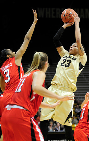 Colorado's Chucky Jeffery (right) takes a shot over Utah's Iwalani Rodrigues (left) and Taryn Wicijowski (middle) during their basketball game at the University of Colorado in Boulder , Colorado January 8, 2013. BOULDER DAILY CAMERA/ Mark Leffingwell