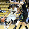 Colorado's Ashley Wilson (left) slides past Oregon's Jasmin Holliday (middle) and Danielle Love (right) during their basketball game at the University of Colorado in Boulder, Colorado March 1, 2012. CAMERA/MARK LEFFINGWELL