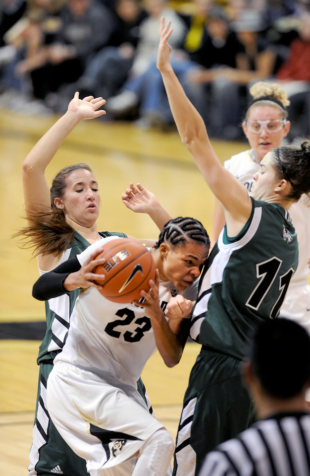 Chucky Jeffery, of Colorado,  drives into Sammie Jensen and past Tina Doughty, both of Utah Valley during the second  half of the December 22, 2012 game in Boulder.<br /> Cliff Grassmick / December 22, 2012