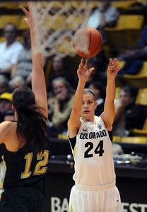 Lauren Huggins of CU fires up a 3-pointer on Sam Martin of CSU. For more photos from CU CSU basketball, go to www.dailycamera.com. Cliff Grassmick / December 5, 2012