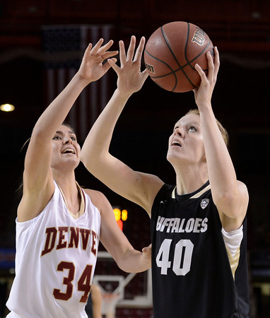 "University of Colorado's Rachel Hargis takes a shot over Theresa Wirth during a games against the University of Denver on Tuesday, Dec. 11, at the Magnus Arena on the DU campus in Denver. For more photos of the game go to  <a href=""http://www.dailycamera.com"">http://www.dailycamera.com</a><br /> Jeremy Papasso/ Camera"
