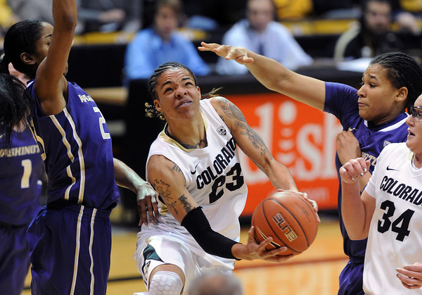 """Chucky Jeffery of CU goes between Aminah Williams, left, and Talia Walton  of Washington during the first half of the Feb. 24th, 2013 game in Boulder, Colorado.<br /> For more photos of the game, go to  <a href=""""http://www.dailycamera.com"""">http://www.dailycamera.com</a>.<br /> Cliff Grassmick / February 24, 2013"""