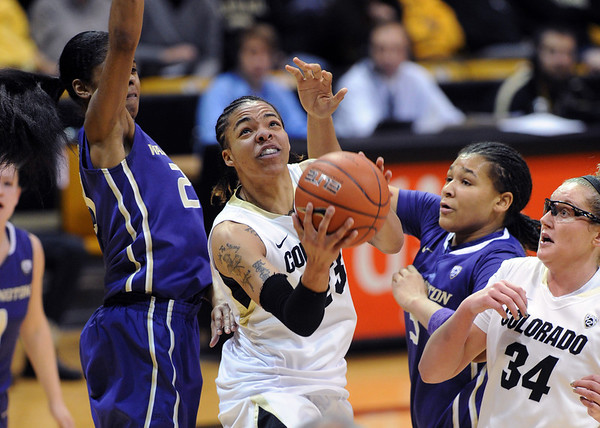 Chucky Jeffery of CU goes between Aminah Williams, left, and Talia Walton  of Washington during the first half of the Feb. 24th, 2013 game in Boulder, Colorado.<br /> <br /> Cliff Grassmick / February 24, 2013
