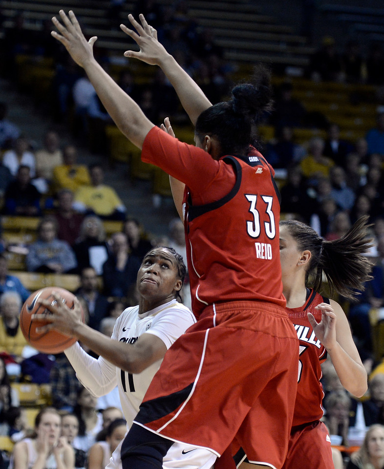 "University of Colorado's Brittany Wilson goes for a shot while being guarded by Monique Reid on Friday, Dec. 14, during a game against Louisville at the Coors Event Center on the CU campus in Boulder. For more photos of the game go to  <a href=""http://www.dailycamera.com"">http://www.dailycamera.com</a><br /> Jeremy Papasso/ Camera"