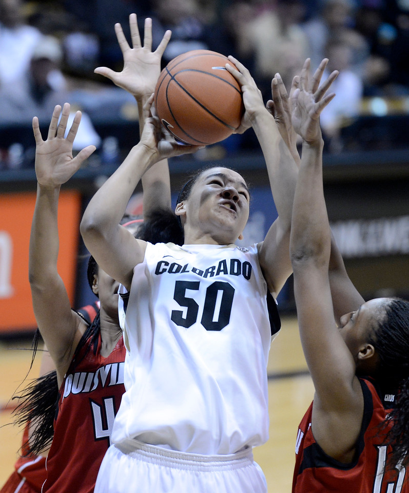 "University of Colorado's Jamee Swan takes a shot over a swarm of defenders including Cortnee Walton No. 14, at right, and Antonita Slaughter, No. 4, on Friday, Dec. 14, during a game against Louisville at the Coors Event Center on the CU campus in Boulder. For more photos of the game go to  <a href=""http://www.dailycamera.com"">http://www.dailycamera.com</a><br /> Jeremy Papasso/ Camera"