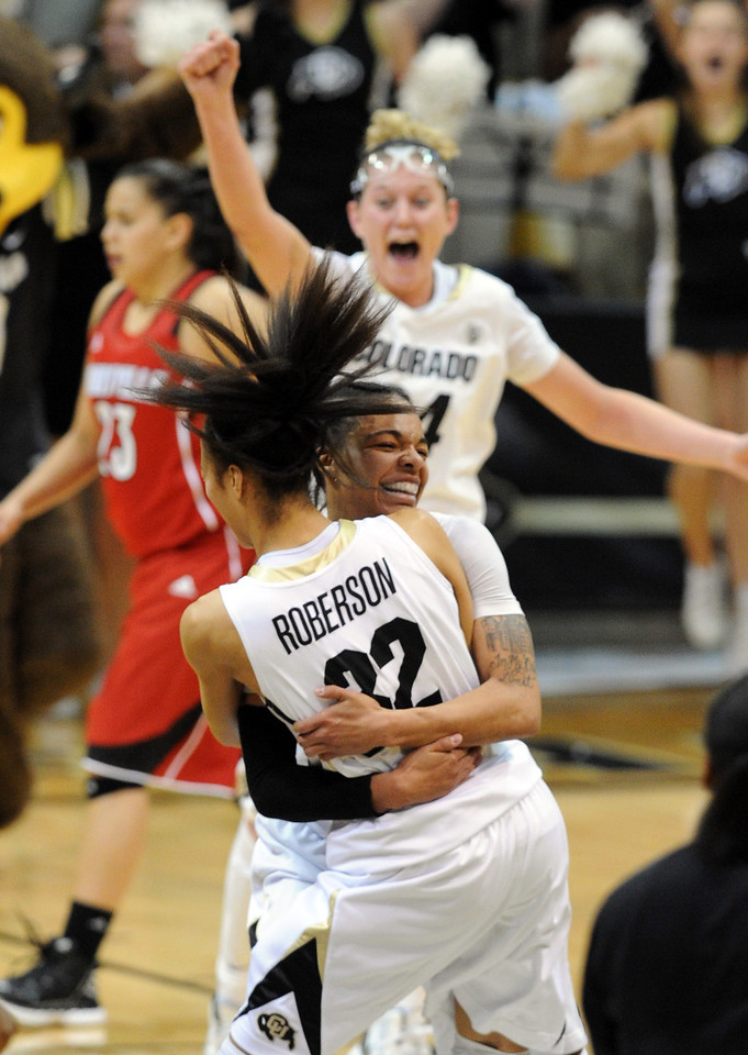 Chucky Jeffery (23) of CU is hugged by Arielle Roberson as the Buffs upset  #8  Louisville.<br /> Cliff Grassmick / December 14, 2012