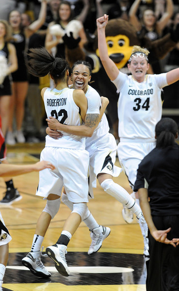 Chucky Jeffery (23) of CU is hugged by Arielle Roberson as the Buffs upset  #8  Louisville. Jen Reese celebrates in the background.<br /> Cliff Grassmick / December 14, 2012