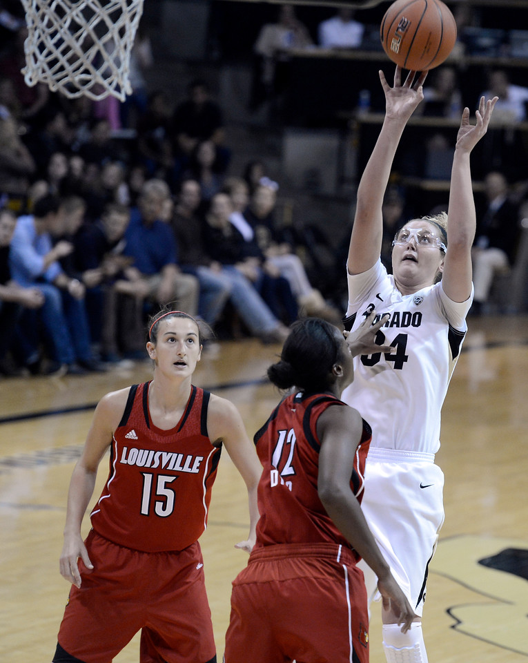 "University of Colorado's Jen Reese takes a shot over Shawnta Dyer, No. 12, and Meghan Dienes, No. 15, on Friday, Dec. 14, during a game against Louisville at the Coors Event Center on the CU campus in Boulder. For more photos of the game go to  <a href=""http://www.dailycamera.com"">http://www.dailycamera.com</a><br /> Jeremy Papasso/ Camera"