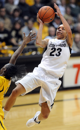 """Chucky Jeffery  of Colorado drives around Eliza Pierre of California<br /> during the first half of the January 12, 2012 game in Boulder.<br /> For more photos of the game, go to  <a href=""""http://www.dailycamera.com"""">http://www.dailycamera.com</a>.<br /> January 12, 2012 / Cliff Grassmick"""