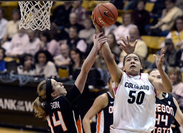 """University of Colorado's Jamee Swan gets fouled by Ali Gibson, No. 14, while going for a shot during a game against Oregon State on Friday, Feb. 8, at the Coors Event Center on the CU campus in Boulder. CU won the game 61-47. For more photos of the game go to  <a href=""""http://www.dailycamera.com"""">http://www.dailycamera.com</a><br /> Jeremy Papasso/ Camera"""