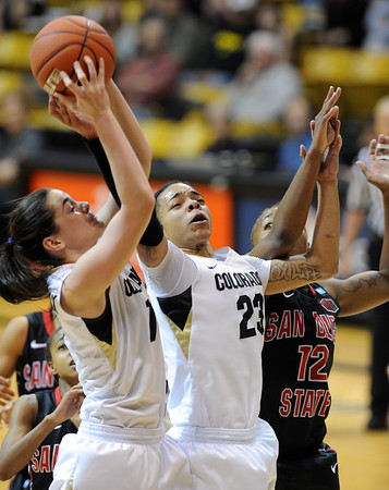 """Meagan Malcolm-Peck, left, and Chucky Jeffery, both of CU, gets a rebound from Deajanae Scurry of SDSU during the second half of the 26th Annual Omni Hotels Classic in Boulder, Colorado, on November 24, 2012.<br /> For more photos of the game, go to  <a href=""""http://www.dailycamera.com"""">http://www.dailycamera.com</a>.<br /> Cliff Grassmick / November 24, 2012"""