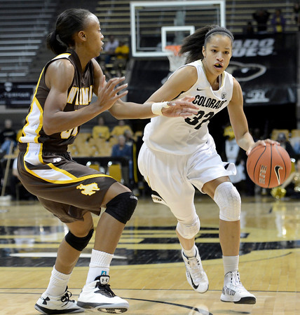 """University of Colorado's Arielle Roberson drives past Chaudra Sewell during a game against the University of Wyoming on Wednesday, Nov. 28, at the Coors Event Center on the CU campus in Boulder. For more photos of the game go to  <a href=""""http://www.dailycamera.com"""">http://www.dailycamera.com</a><br /> Jeremy Papasso/ Camera"""