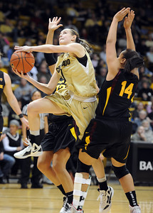 Lexy Kresl of Colorado, drives between Alex Earl, left, and Adrianne Thomas of Arizona State during the first half of the February 11, 2012 game in Boulder.  February 11, 2012 / Cliff Grassmick