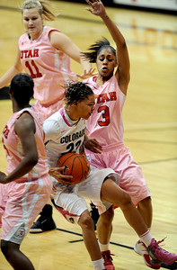 Chucky Jeffery of Colorado, drives into the Utah defense, including Iwalani Rodriques, during the second half of the February 18, 2012 game in Boulder. February 18, 2012 / Cliff Grassmick