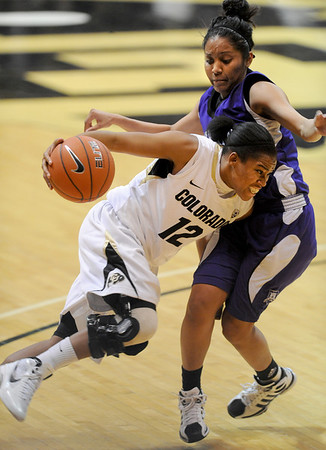 """Ashley Wilson of Colorado  drives past Justine Johnson of Weber State. <br /> For more photos of the game, go to  <a href=""""http://www.dailycamera.com"""">http://www.dailycamera.com</a>.<br /> December 17, 2011 / Cliff Grassmick"""