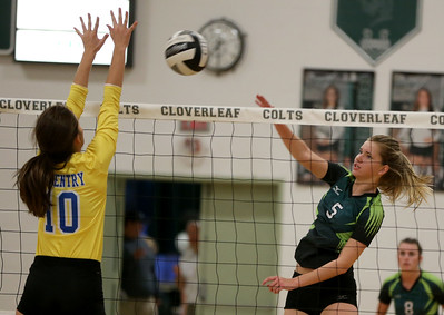 Cloverleaf's Kristen Hall hits the ball off of Coventry blocker Ashley Mirka for a point during game one of their match. AARON JOSEFCZYK / GAZETTE