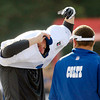 Punter Pat McAfee talks to a coach through his jersey as he puts it on at the start of practice.