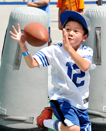 John P. Cleary | The Herald Bulletin<br /> Carter Cosgrove, 6, from Carmel, reaches to catch the football after running through the tackling dummies at the Play 60 Zone in Colts City Monday afternoon. Carter's family had a hard time getting him away from the fun zone so they could go watch the Colts practice.
