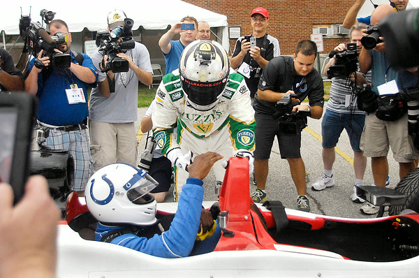 John P. Cleary | The Herald Bulletin<br /> Race car driver Ed Carpenter helps Colts wide receiver Reggie Wayne out of the IndyCar 2-seater after driving him into the Colts Training Camp at AU Wednesday morning.