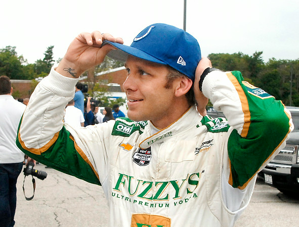 John P. Cleary | The Herald Bulletin<br /> IndyCar drive Ed Carpenter puts on a Colts hat after driving Reggie Wayne to training camp in a IndyCar 2-seater race car.